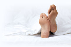 Person's foot in bed Royalty Free Stock Image