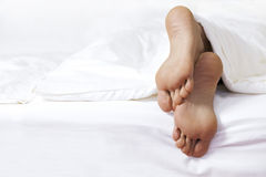Person's foot in bed Royalty Free Stock Photos