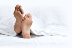 Person's foot in bed Royalty Free Stock Images