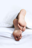 Person's foot in bed Royalty Free Stock Photo