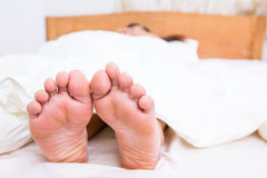 Person`s foot in bed Royalty Free Stock Photos