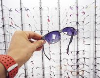 Person`s hand choosing a glasses sunglasses at the optics store. Stand with glasses in the store of optics stock photos