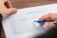 Person's hand filling blank weekly time sheet Royalty Free Stock Image