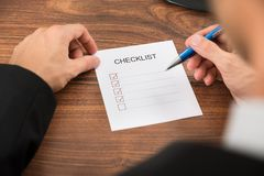 Person's hand filling checklist Royalty Free Stock Image