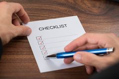 Person's hand filling checklist Royalty Free Stock Photo