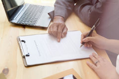 Person& x27;s hand hold ballpoint pen writing on  agreement paper she. Woman& x27;s hand hold ballpoint pen writing on  agreement paper sheet, fill in document Royalty Free Stock Photo