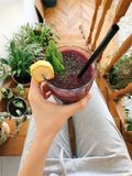 Person's Hand Holding Drinking Glass Filled With Smoothie stock photography