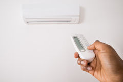 Person's Hand Holding Remote To Operate Air Conditioner Stock Images