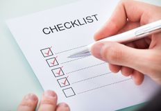Person's hand marking on checklist with pen Royalty Free Stock Photography