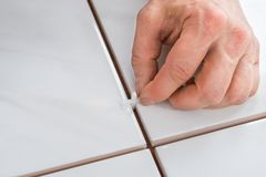 Person's hand placing spacers between tiles Royalty Free Stock Photo
