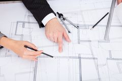 Person's hand pointing on blue print Stock Photo