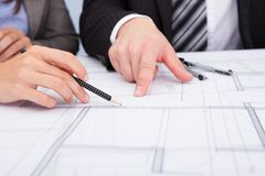 Person's hand pointing on blue print Royalty Free Stock Image