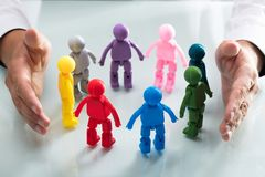 Person protecting multi colored human figures. A person`s hand protecting multi colored human figures forming circle royalty free stock images