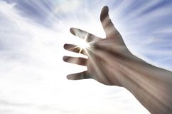 Person's Hand Reaching Towards Heaven Sunlight. Persons hand reaching in hope towards heaven with sunlight shining through royalty free stock images