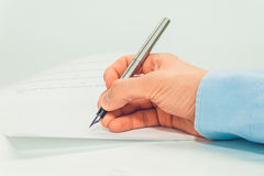 Person& x27;s hand sign document Royalty Free Stock Image