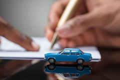 Person`s Hand Signing Car Loan Agreement Contract. A Person`s Hand Signing Car Loan Agreement Contract With Car Toy On Glass Desk stock images