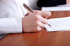 Person's hand signing document Stock Photo