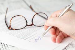 Person& x27; s-hand som undertecknar ett viktigt dokument arkivfoto
