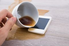 Person's hand spilling coffee on cellphone Royalty Free Stock Photos