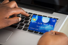 Person's Hand Using Debit Card While Shopping Online. Close-up Of A Person's Hand Using Debit Card While Shopping Online On Laptop Royalty Free Stock Photos