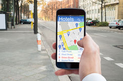 Person's Hand Using GPS Navigation In Cellphone. Close-up Of Person's Hand Using GPS Navigation In Cellphone To Find Hotels Stock Images