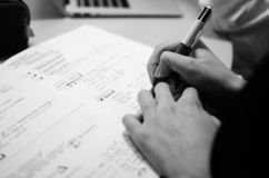 Person`s hand, writing something in a notebook royalty free stock photos