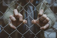 Person`s hands on a chain linked fence. A depressing shot of a person`s hands on a chain linked fence stock image