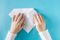 Person`s hands folding a paper airplane. On a blue background stock image