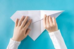 Person`s hands folding a paper airplane Stock Photos