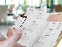 Person`s hands holding menu and mobile phone in restaurant. A foreign man in cafe ordering food using word translation program wh stock image