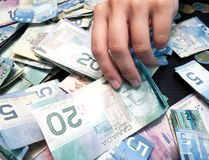 Person's hands picking Twenty Canadian Dollar Bill. From heap of paper currency Stock Photo