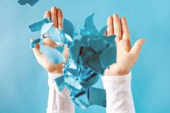 Person`s hands throwing paper pieces. Person`s hands throwing crumpled paper pieces into the air stock photography