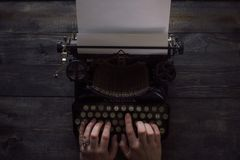 Person`s hands writing on a vintage typewriter royalty free stock photo