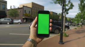 POV Turning in Small Town with Green Screen Smartphone. 8496 A person`s perspective turning in the business district in a small town while holding a green screen stock footage