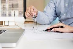 Person& x27; s-tekniker Hand Drawing Plan på blått tryck med architec Royaltyfria Bilder