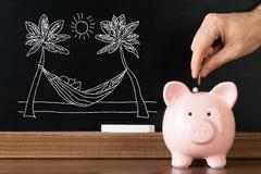 Person Saving Money In Piggybank para férias Imagens de Stock