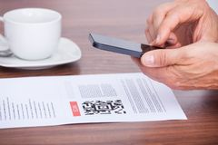 Person scanning barcode using cellphone Stock Photo