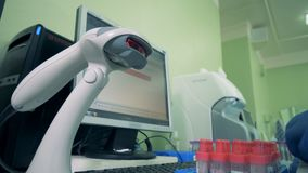 Worker scans tubes with blood, close up. A person scans barcodes on tubes, using special equipment stock video