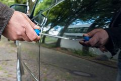 A person scratches the car door on a car with a screwdriver stock photo