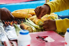 Person selling grilled corn outdoors in summer. Royalty Free Stock Images