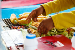 Person selling grilled corn outdoors in summer. Royalty Free Stock Image