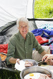 Person serving senior man fried breakfast on camping trip, man sitting inside tent, smiling, portrait Royalty Free Stock Photography