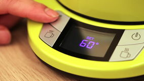 Person setting electric tea kettle temperature to 60 C (140F) stock footage
