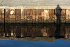 Person shadow on rusty pier Stock Images