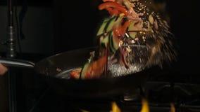 Person Shakes Cut Vegetables på pannan ovanför den öppna flamman lager videofilmer