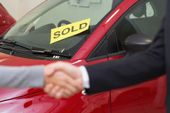 Person shaking hands in front of a sold car Royalty Free Stock Photos