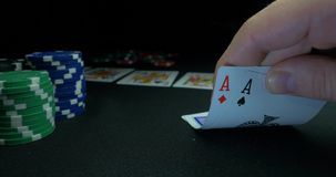 Person showing his deck at the poker game. Card player checks his hand, two aces in, chips in background on green stock video footage