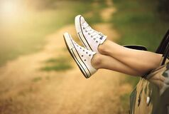 Person Showing Its Feet Wearing White Sneakers Royalty Free Stock Photo