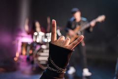 Person showing sign of the horns while rock band playing Stock Photos
