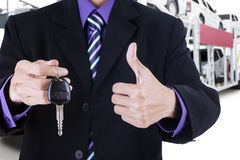 Person shows a car key with trailer truck background Royalty Free Stock Photography